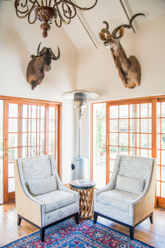 African Hunting The Lounge - two chairs and a table with dear heads hanging from the walls.